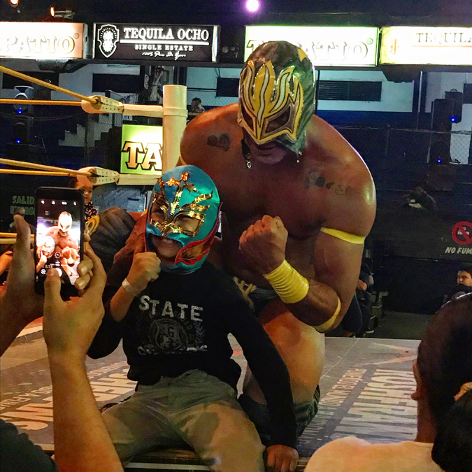 A luchador and young fan posing for pictures at a wrestling match