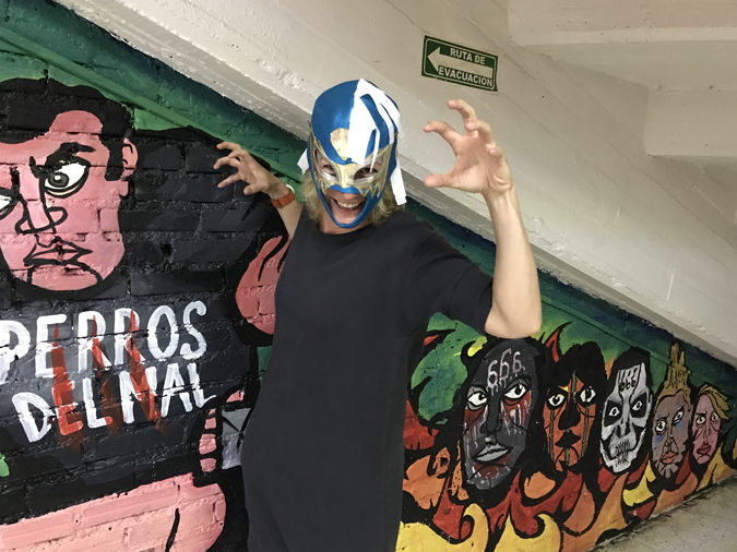 A crazy woman posing in a lucha libre mask